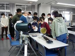 講座風景 光の反射を利用した装置の説明を受ける受講生